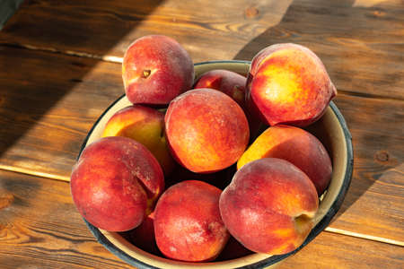 ripe peaches in an iron bowl on a wooden background