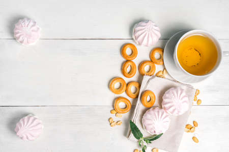 cup of green tea with sweets, top view. bagels, nuts and tender marshmallows on a light background Stock fotó