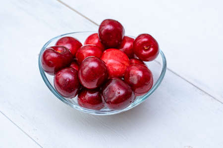 Glass vase in the form of a bowl with ripe cherries stands on a white wooden background. Stock fotó