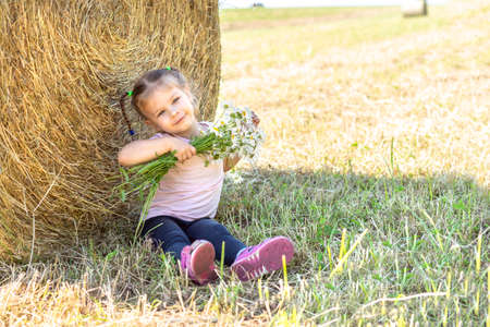 cute little girl eating corn sticks and happy. gesture of pleasure and delight Stock fotó