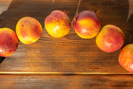 ripe juicy nectarines on a wooden background. space for text, close-up