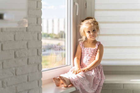 beautiful little girl 4 years old in a pink dress sits on the window on a sunny day and smiles
