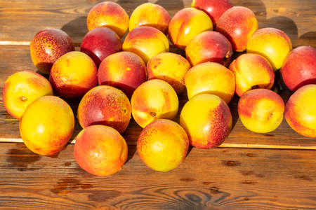 a lot of ripe nectarine on a wooden table Stock fotó