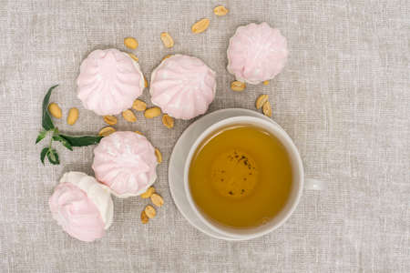 cup of green tea with sweets, top view. bagels, nuts, a mint leaf and tender marshmallows on a light background