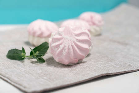 delicate light marshmallows with a mint leaf on a light background