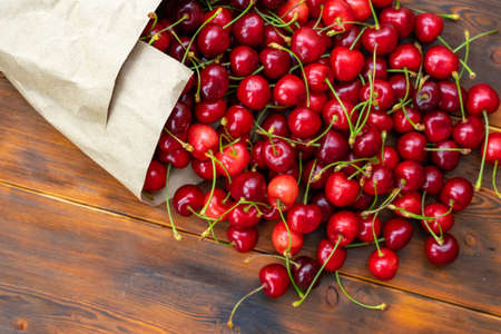 ripe juicy cherries in a paper bag spilled on on a wooden table, selective focus