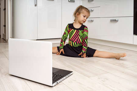 little girl in a gymnastic leotard is engaged in online gymnastics at home and looks at a laptop. sitting on a twine