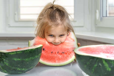 cute baby sits at home at the table and eats a piece of watermelon with gusto