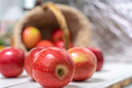 red juicy fresh apples on a wooden background spilled out of the basket