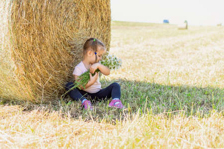 a child with a bouquet of field daisies sat down to rest near a haystack on a summer day
