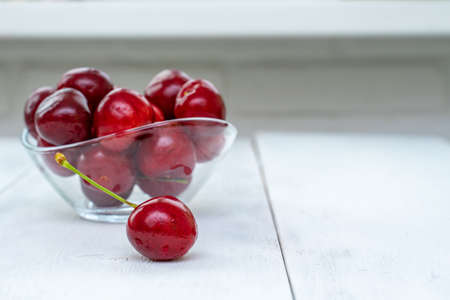 A heap and a large glass bowl of fresh red ripe cherries on a white wooden background