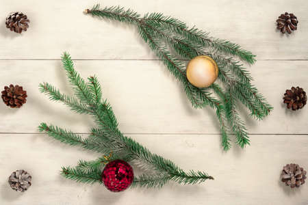 Christmas background with fir branches and decorations on old wooden table. Space for text or design. Top view.