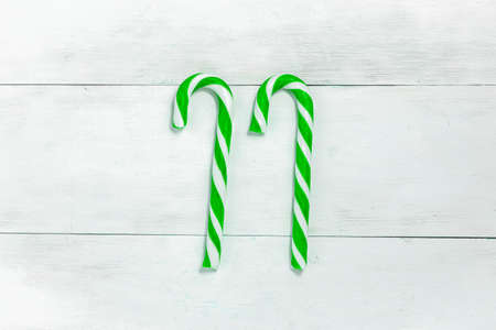 2 candies christmas canes of green color on a light wooden background