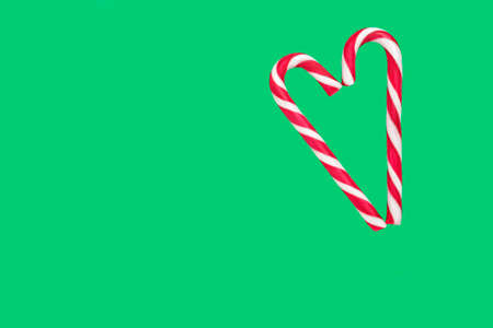 candy cane in the form of a heart on a green background, isolate