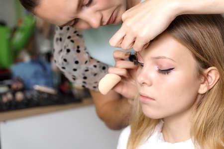 make-up artist makes makeup 16 years old beautiful girl. applying mascara to eyelashes