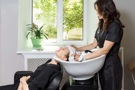hairdresser covers client's hair with a towel. young woman gets a hair wash in a beauty salon