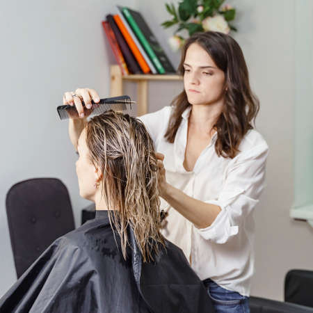 beautiful woman stylist makes a haircut to a blonde client