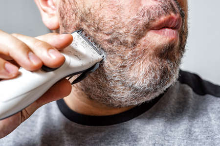 gray-haired man cuts his beard with an electric clipper