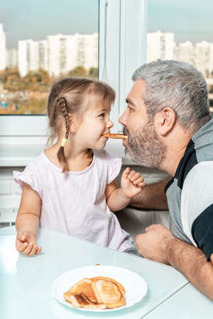 senior dad and little daughter laugh and eat pancakes together. the concept of family and spending time together