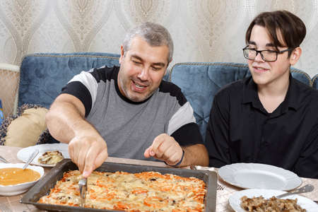 father cuts homemade pizza with a round knife at family dinner. family concept