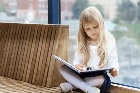 cute little girl in business style writes in a notebook