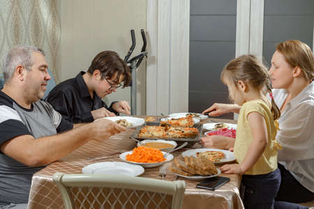 Caucasian family of mom, dad, son and daughter have dinner at home with pizza. homemade dinner with family and lifestyle