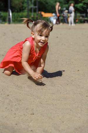 a little girl crawls on the sand and laughs. summer vacation concept Reklamní fotografie