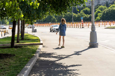 slender girl in a short skirt rides a skateboard down the street