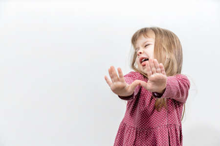 the little girl threw her arms forward in a rejection position. human emotions. mock up with copy space