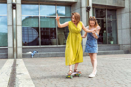 Daughter helping mum on skateboard. Outdoor lifestyle picture on a sunny summer day.