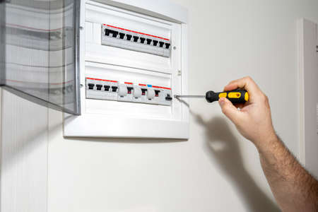 Electrician installing panel with electric meter in apartment of customer