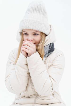 beautiful blonde girl breathes on frozen hands. winter cold Banco de Imagens