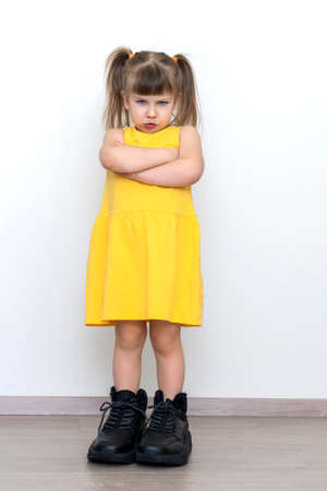 offended little girl in yellow dress posing in huge mens boots against gray wall