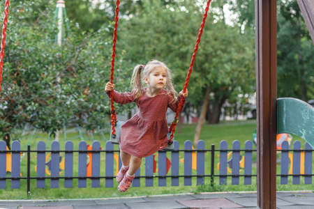 caucasian child girl in red polka dot dress swinging on a swing on a summer day. summer children's games and fun outdoors.