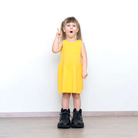 little girl in big daddy boots standing over gray background with surprise face pointing finger to up, idea concept