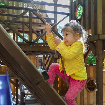 little girl in a yellow jacket and pink pants on the playground. Child climbing rope outdoor Children healthy summer activity Healthy growth