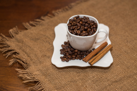units: coffee beans and cinnamon white cup and saucer on a table brown texture units large lot of grain