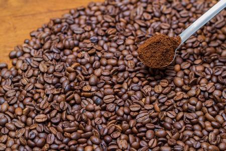 invigorate: coffee beans and metal spoon on a table brown metal texture close a lot of ground grain Stock Photo