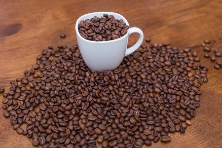 coffeebeans: coffee beans white cup on a desk brown texture close a lot of grain Stock Photo