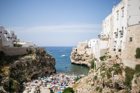 Beautiful beach with people in Polignano a Mare in the southern part of Italy crystal clear azure water