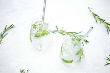 Beautiful glass of water or mojito with lime and mint cocktail on the gree background and white table summer vibe and atmosphere Reklamní fotografie