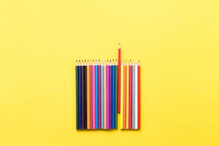 Colorful pencils on the yellow background outer space for text place Imagens