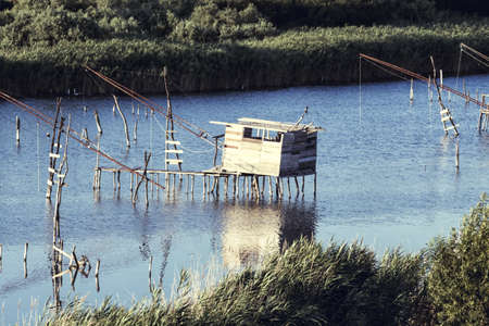 Fish farming,traditional fishing net, Old Fish trap at laguna in Ulcinj in Montenegro. Fisherman Cabins at Port Milena Canal. Old fishing pile dwellings in one of the Adriatic country Reklamní fotografie