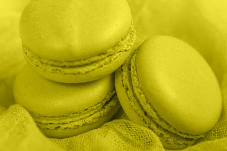 Delicious french dessert. Three gentle soft pastel yellow cakes macaron or macaroon on airy fabric,
