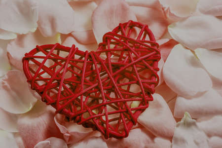 Decorative coral wooden heart made of rattan on pink rose petals background. Selective focus