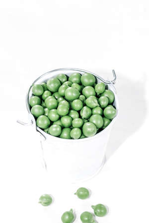 Food diet concept with fresh green peas in a white bucket on white background. 免版税图像