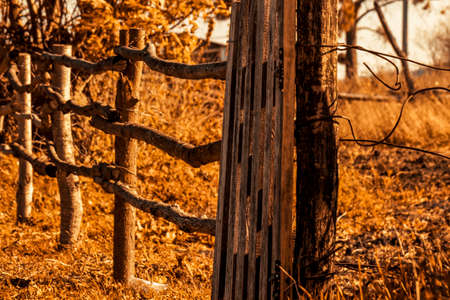 old broken wooden fence in an abandoned village in autumn. Nostalgia for childhood in the countryside. Stock fotó