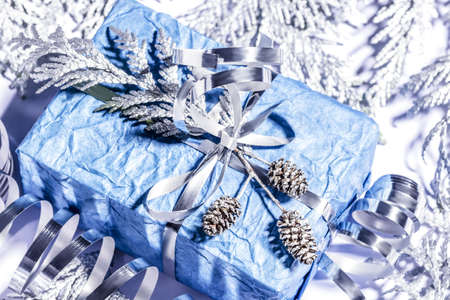 Christmas presents with handmade gift box in silver blue color decorated with pine cones and twigs on white background, preparation for holidays. Selective focus.