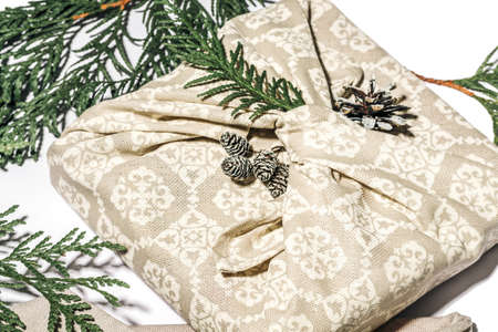 Zero waste gift wrapping traditional Japanese furoshiki style. Beige hand made gift package for Christmas with fabric, thuja and cone on white. Ecological concept eco-friendly decor xmas. Close up Stock fotó