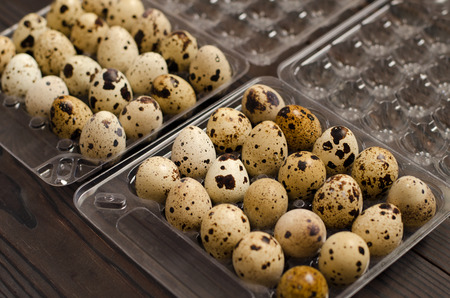 Quail eggs in a plastic container on a dark wooden background. Close up